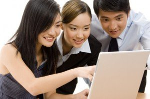 A group of three smiling business people working at a laptop computer